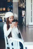 Beautiful girl in white outfit drinking Martini in a bar Stock Photo