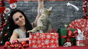 Beautiful girl with a white puppy in holiday spirit surrounded by New Year`s decoration stock footage