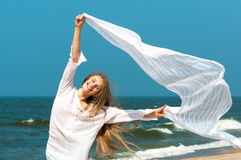 Beautiful girl with white scarf on a beach Stock Image