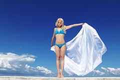 Beautiful Girl With White Scarf over blue sky. Royalty Free Stock Image