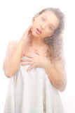Beautiful girl in a white sheet behind a wet glass Royalty Free Stock Photos