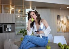 Beautiful girl in a white shirt and blue jeans with a green Apple