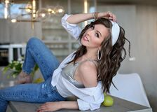 Beautiful girl in a white shirt and blue jeans on a table with a green Apple