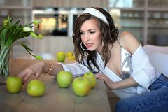 Beautiful girl in a white shirt and blue jeans at a table with green apples