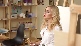 Portrait of a sexy girl artist with paintbrushes in hand in front of the canvas. A beautiful girl in a white shirt with brushes for drawing in her hand sits in stock video