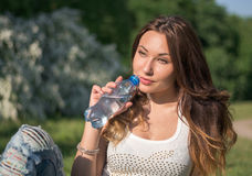 Beautiful girl in a white shirt is drinking water from a bottle Royalty Free Stock Photos