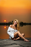 Beautiful girl with a white shirt on the pier at sunse Royalty Free Stock Photography