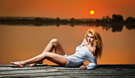 Beautiful girl with a white shirt on the pier at sunse Stock Photos