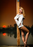 Beautiful girl with a white shirt on the pier at sunse Royalty Free Stock Images