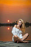 Beautiful girl with a white shirt on the pier at sunset Stock Photos