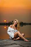 Beautiful girl with a white shirt on the pier at sunset Royalty Free Stock Photography