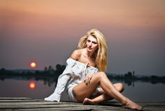 Beautiful girl with a white shirt on the pier at sunset Royalty Free Stock Images