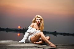 Beautiful girl with a white shirt on the pier at sunset Royalty Free Stock Photos