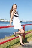 Beautiful girl in white striped dress on the seashore Royalty Free Stock Photography