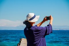 Beautiful girl in white summer hat and blue shirt on the beach makes selfie, photo. Stories from vacation for internet royalty free stock images