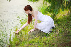 The beautiful girl in a white sundress on the bank Royalty Free Stock Photos