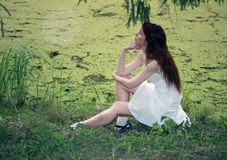 Beautiful girl in a white sundress on the bank of wood lake Stock Photography