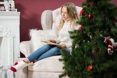 красивая девушка  сидит с книгой около рождественской елки Stock Photography