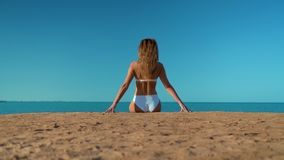 The beautiful girl in a white swimsuit sitting on the background of the sea stock video