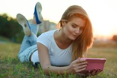 Beautiful girl in white T-shirt and jeans lying in the grass on the field talking to someone via her tablet pc Royalty Free Stock Image