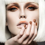 Beautiful girl in a white wig, with gold makeup and nails. Celebratory image. Beauty face. royalty free stock photo