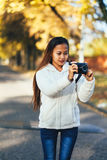 Beautiful girl in white woolen coat photographing outside on the street during autumn afternoon Stock Images