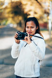 Beautiful girl in white woolen coat photographing outside on the street during autumn afternoon.  Stock Images