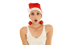 Beautiful girl whith Christmas hat. A beautiful girl wearing a Christmas hat and decorative balls as earings Royalty Free Stock Images