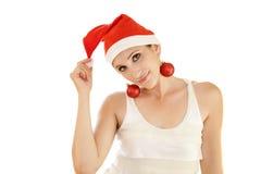 Beautiful girl whith Christmas hat. A beautiful girl wearing a Christmas hat and decorative balls as earings Stock Photos