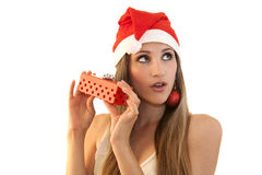 Beautiful girl whith Christmas hat. A beautiful girl wearing a Christmas hat and decorative balls as earings, holding a present Stock Photo
