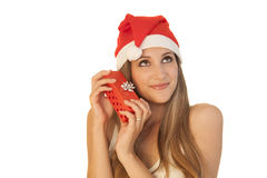 Beautiful girl whith Christmas hat. A beautiful girl wearing a Christmas hat and decorative balls as earings, holding a present Stock Photography