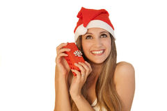 Beautiful girl whith Christmas hat. A beautiful girl wearing a Christmas hat and decorative balls as earings, holding a present Stock Images