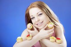 Beautiful girl who eats cakes Stock Photos