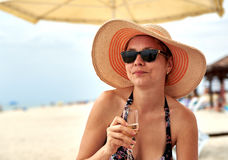 Beautiful girl in wide-brimmed hat drinking champagne Royalty Free Stock Photos