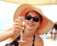 Beautiful girl in wide-brimmed hat drinking champagne Royalty Free Stock Images