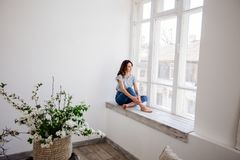 Beautiful girl by the window. stock images