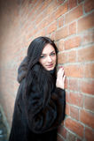 Beautiful girl in winter against a brick wall. Royalty Free Stock Photo