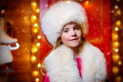 Beautiful girl in winter clothes. Portrait of a beautiful nine-year-old girl in a fur hat and scarf near her house decorated for Christmas royalty free stock image