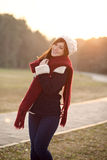 Beautiful girl in winter clothes smiling with sunset Stock Photo