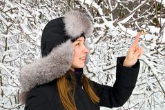 Beautiful girl in winter clothing. Staying in a winter woods Royalty Free Stock Photography
