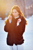 Beautiful girl in winter fur coat. Backlit sunset sunshine Stock Photo