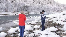 The photographer in winter, photographing the girl near the mountain river on a snowy background. Beautiful girl in winter jacket and hat posing for the stock footage