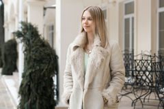Beautiful girl in the winter jacket standing near the building. Outdoors Royalty Free Stock Photos
