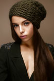 Beautiful girl in winter knit hat and khaki jacket. Young model with gentle make-up and colored arrows. Warm winter picture. Beauty face Royalty Free Stock Photos