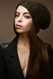 Beautiful girl in winter knit hat and khaki jacket. Young model with gentle make-up and colored arrows. Warm winter picture. Beauty face Royalty Free Stock Photo