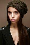 Beautiful girl in winter knit hat and khaki jacket. Young model with gentle make-up and colored arrows. Warm winter picture. Beauty face Royalty Free Stock Photography