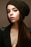 Beautiful girl in winter knit hat and khaki jacket. Young model with gentle make-up and colored arrows. Royalty Free Stock Photography
