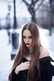 Beautiful girl in the winter landscape. Beautiful girl with bright makeup and black coat in the winter landscape Royalty Free Stock Photos