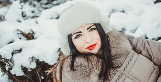 Beautiful girl in winter park, fir-trees covered with frost and snow Stock Images