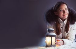 Beautiful girl on winter snow with christmas lantern royalty free stock photography